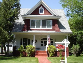 The front of the inn shows a landscaped lawn and red Victorian exterior.