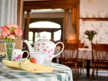 A tea pot and cup rests on a checkered cloth table with fresh pastries and carnations.