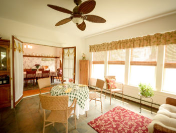 The sunroom shows antique furnishings, a small seating area, and a couch.