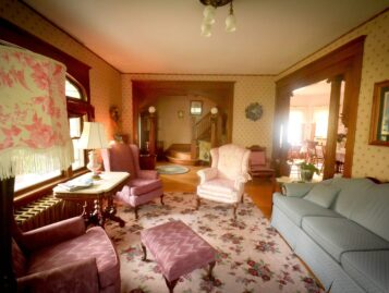 The parlor shows antique furnishings and ample seating options.