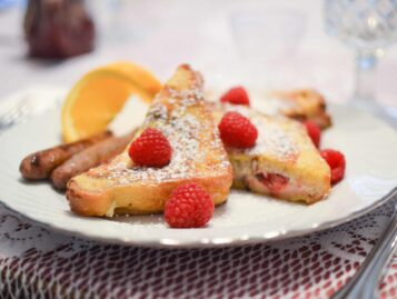 Stuffed french toast is topped with fresh raspberries and powdered sugar.