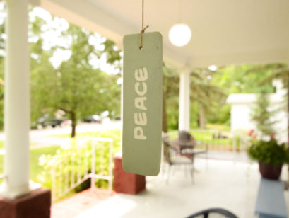 A room tag reading 'Peace' dangles in front of the porch