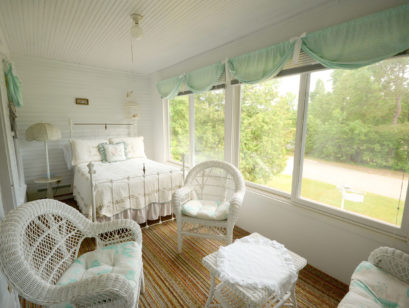 One of the rooms overlooks the front lawn and boasts ample seating and a plush bed